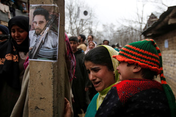 A woman mourns as she walks past a poster of Mudasir Khan, a suspected militant, who according to local media was killed during a gun battle with Indian security forces on Sunday, during his funeral in Midoora village in south Kashmir's Pulwama district