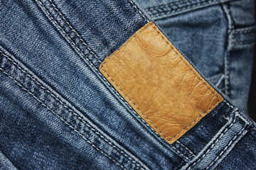 Leather tag on denim blue jeans background. Empty brown leather label sewed on classic jeans, close up view of casual classic jean apparel mock up