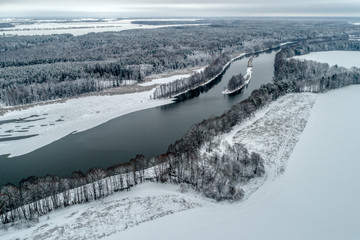 Winter landscape with a river flowing through the winter forest.
