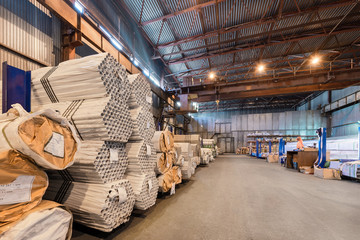 Factory warehouse metal rolled. Bundles of steel pipes stacked