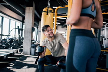 Handsome young man in sportswear talking to a fit woman at the gym.