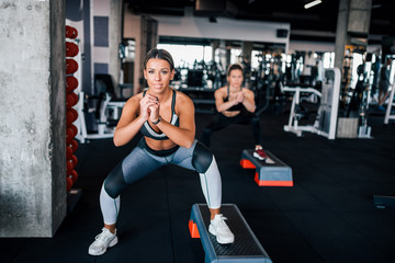 Fit women exercising on steppers.