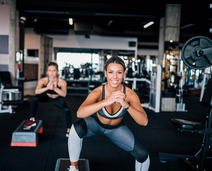 Two beautiful fit sports women exercising with steppers, front view.