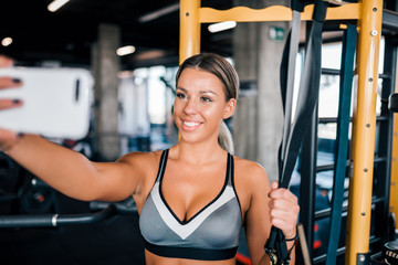 Attractive young woman in sportswear taking selfie at the gym.