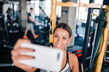 Smiling female athlete taking selfie.