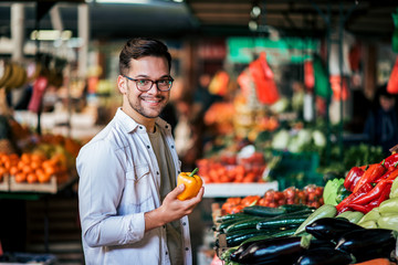 Handsome millenial man buying fresh vegetables at street market.