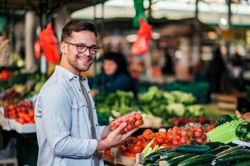 Buying fresh vegetables at street market.