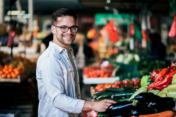 Portrait of a handsome young man buying fresh vegetables, smiling at camera.