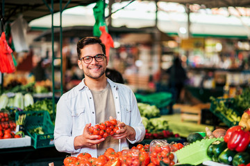 Young man at farmer's market with cherry tomatoes, smiling at camera. Healthy eating and people concept.