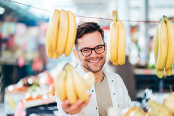 Young man buying or selling bananas at farmer's market.