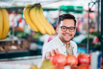 Smiling young man buying fresh fruit at market outdoors.