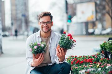 Young man at florist shop outdoors.
