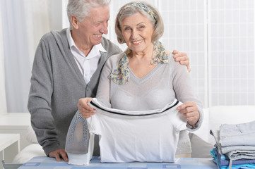 Portrait of happy senior couple during ironing at home