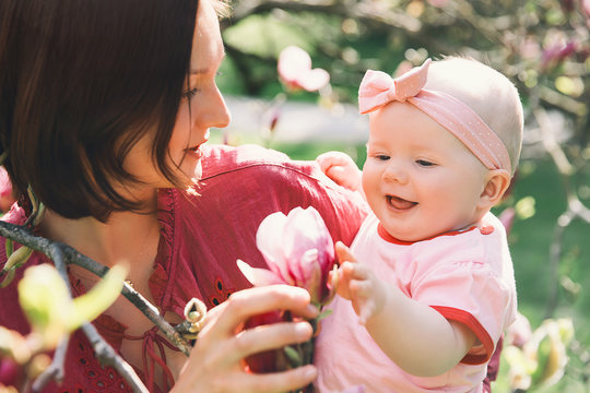 Mother and baby with blooming pink magnolia flower