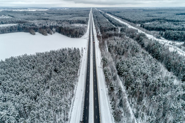 Freeway passing through the winter forest. The road goes away to the horizon line.