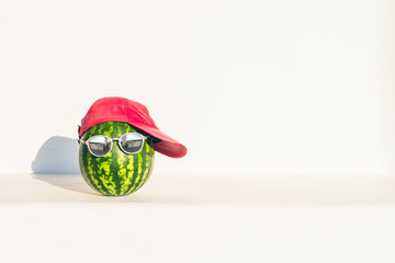Creative and summer picture of watermelon in the form of a human head in the sunglasses headphones and red cap on the white wall background.  concept