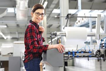 Praca w drukarni. Kobieta obsługuje foliarkę do druku.