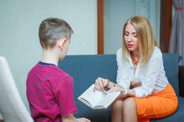 Woman psychologist speaks with a child patient