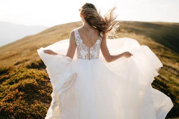 Stylish bride standing on beautiful landscape of mountains on sunset