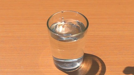 Fototapete - Drop homemade ice cubes into a glass filled with fresh water on a wooden table in Slow Motion