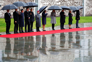 Members of the delegations of German Chancellor Angela Merkel and Latvian Prime Minister Krisjanis Karins are seen before military honours at the Chancellery in Berlin