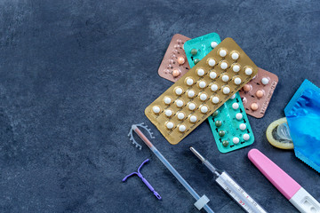 Choosing method of contraception : Birth control pills, an injection syringe, condom, IUD-method, on grey