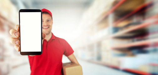 young smiling delivery service courier showing blank smart phone at warehouse. copy space