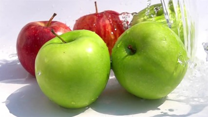Fototapete - Pouring fresh water on the green and the red apples in Slow Motion