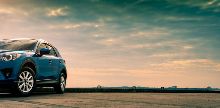 Blue compact SUV car with sport and modern design parked on concrete road by the sea. Hybrid and electric car technology concept. Car parking space. Automotive industry. Car care service concept.