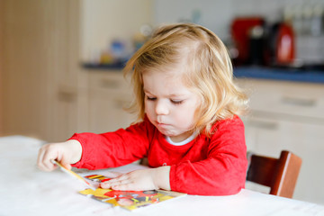Adorable little toddler girl blonde child, playing with puzzles at home or kindergarten. Cute happy healthy child puzzling and making picture. Development and education step for baby