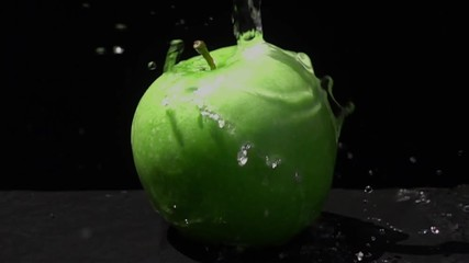 Fototapete - Pouring fresh water on a green apple on black background in Slow Motion