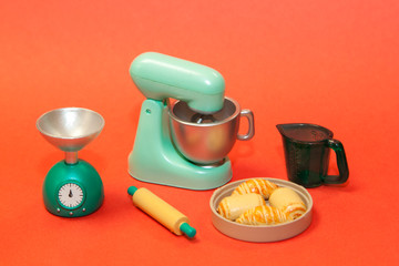 cooking machine to prepare the dough, measuring Cup, rolling pin, scales, and the finished cakes on an orange background