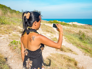 Thai woman is taking a photo at the coast of Thailand
