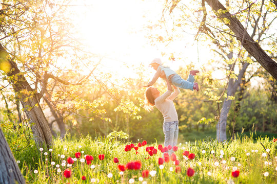 Family mom with daughter woman with child in spring stand and hug on a glade with green grass and tulips