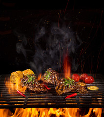 Tasty Beef steaks on iron cast grate with fire flames.