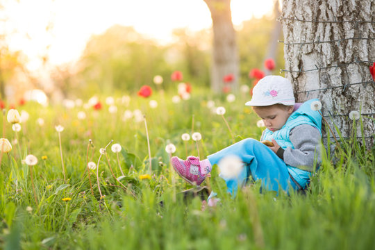 girl child plays on the smartphone leg to the leg in a field with green grass and blooming tulips