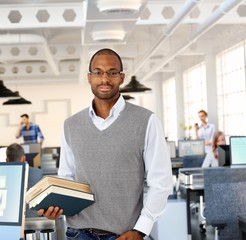 Intelligent black man at office holding books