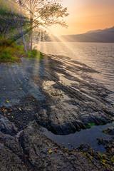bright sun rays shine down on rocky shore
