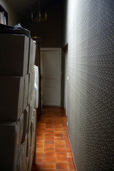 Storage.  Moving in, stacks of cartons stored at narrow corridor in vintage style decorated apartment.