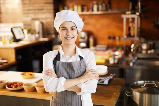 Waist up portrait of young cook smiling at camera while posing in restaurant kitchen, copy space