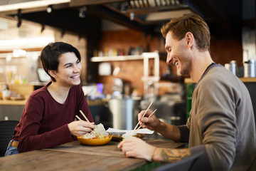 Side view portrait of happy young couple enjoying Asian food in restaurant, copy space