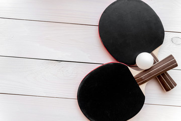 black racket for ping pong ball wooden background top view