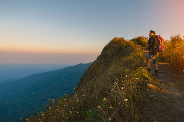 Hipster young man with backpack enjoying sunset on peak mountain. Tourist traveler on background valley landscape view mockup.