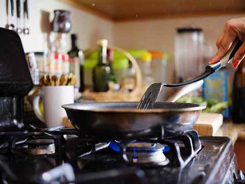 stirring strips of beef in hot skillet inside home kitchen on gas stove