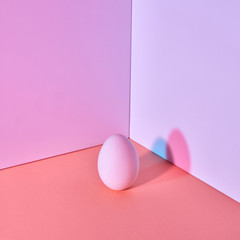 Easter color egg on a multi-colored lilac coral-purple background with a reflection of blue-pink shadows and copy space. Creative layout.