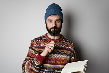 Handsome bearded man in blue beanie thinking with pen and notebook over background