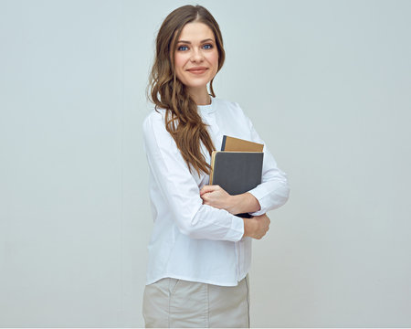 Smiling woman teacher wearing white shirt holding books.