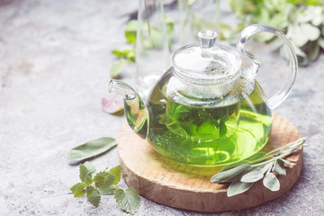 Hot herbal sedative mint tea drink in a glass teapot on wooden tray with fresh garden mint and sage leaves over gray background