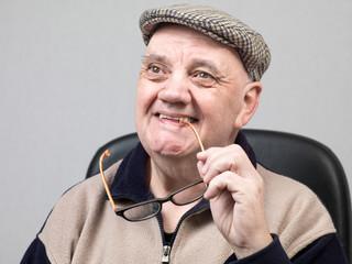 portrait vieil homme tout sourire sur fond gris