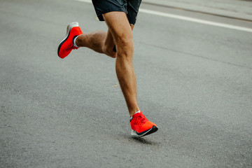 Fototapete - legs man runner in bright red shoes running on asphalt